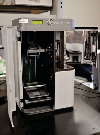 Imagen: La impresora Projet 1200 3D fue capaz de producir fácilmente y perfeccionar el dispositivo usando materiales amigables con el ambiente para hacer dispositivos de bajo costo, para los puntos de atención que detectan rápidamente la anemia a partir de una gota de sangre (Fotografía cortesía de la Universidad del Estado de Kansas).