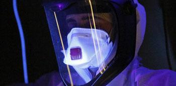 Imagen: Un cribado con luz ultravioleta para líquidos que contienen potencialmente el Ébola (Fotografía cortesía del Departamento para el Desarrollo Internacional DFID-Reino Unido).